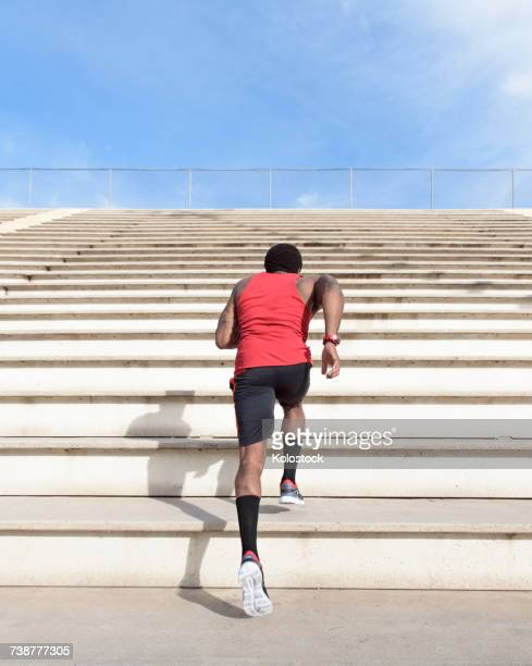 african american man running on bleachers - staircase stock photos and pictures