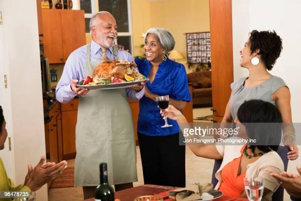african american man serving thanksgiving turkey - african american family dinner - fotografias e filmes do acervo