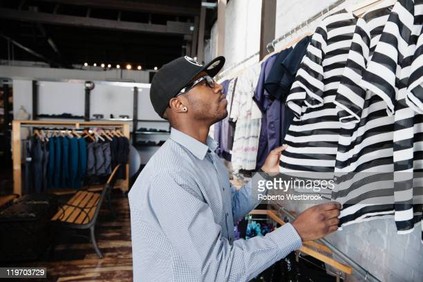 african american man shopping in clothing store - clothing store stock pictures, royalty-free photos & images