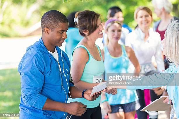 african american man signing up for marathon or 5k race - voter registration bildbanksfoton och bilder