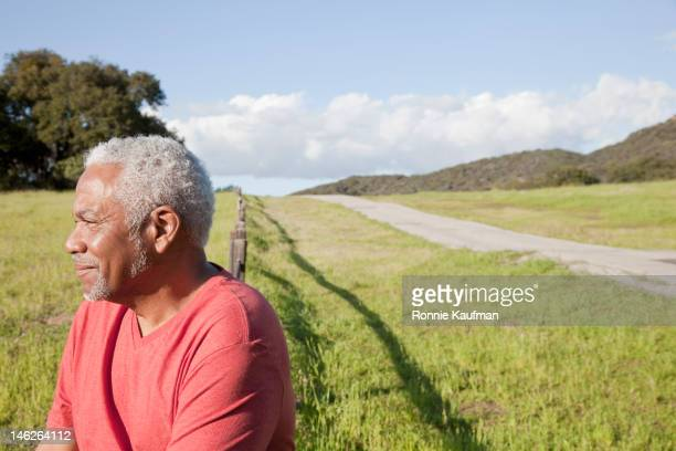 African American man sitting on fence