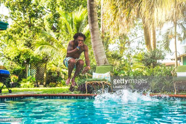 african american man splashes into backyard pool - swimming pool stock pictures, royalty-free photos & images