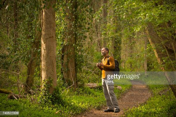 African American man standing on path in forest holding binoculars