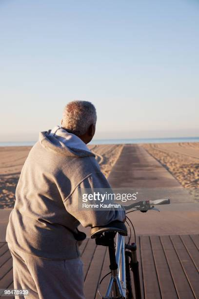 African American man standing with bicycle on beach