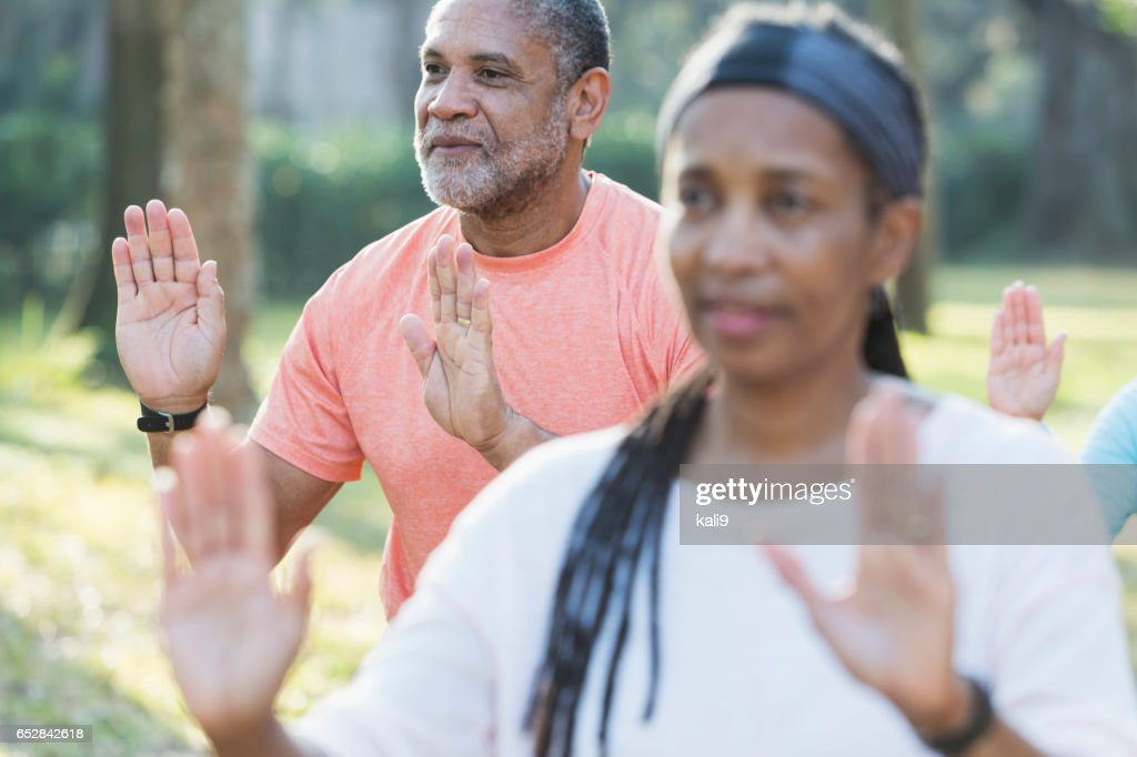 African American man taking tai chi class in park : Stock Photo
