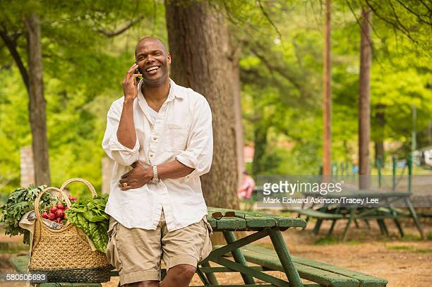 african american man talking on cell phone on picnic table - black shorts stock pictures, royalty-free photos & images