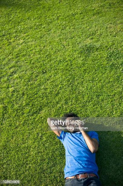 African American man using cell phone laying on grass