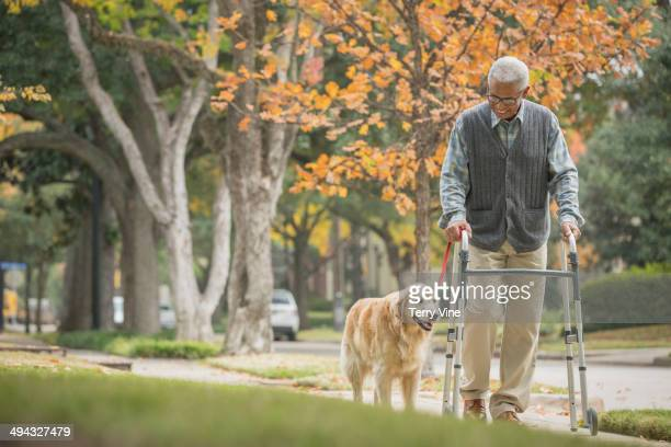 African American man using walker with dog