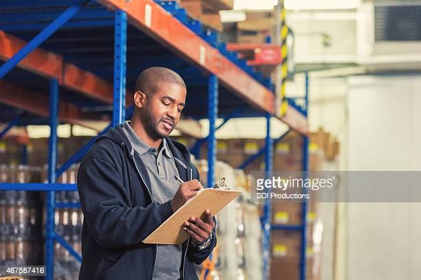 African American man volunteeering in food bank warehouse, taking inventory