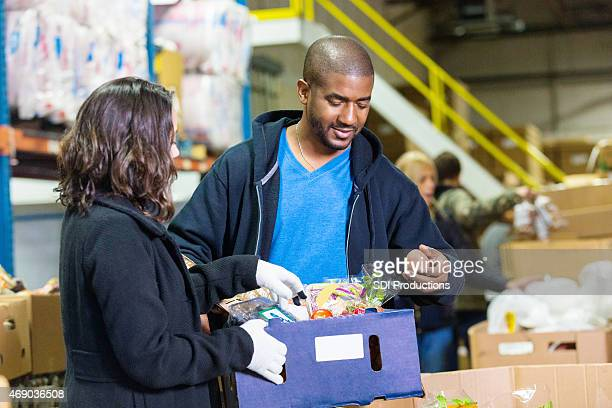 African American man volunteering in food bank with Hispanic woman