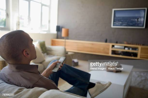 african american man watching television - flat screen stock pictures, royalty-free photos & images
