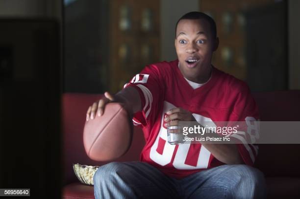 african american man watching television with football and beer - american football sport stock pictures, royalty-free photos & images