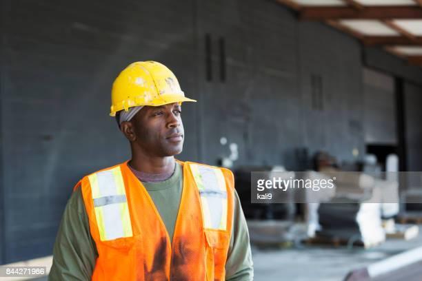 homem afro-americano a usar colete de segurança e capacete de segurança - capacete de obra - fotografias e filmes do acervo