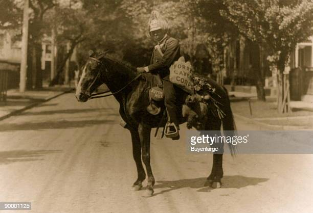 African American man wearing plumed helmet on horse carrying dead chicken canteen labeled buttermilk etc