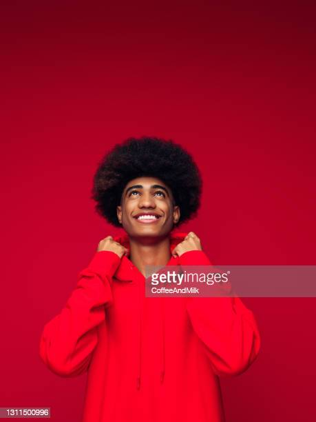 african american man with african hairstyle standing over isolated red background - hooded top stock pictures, royalty-free photos & images
