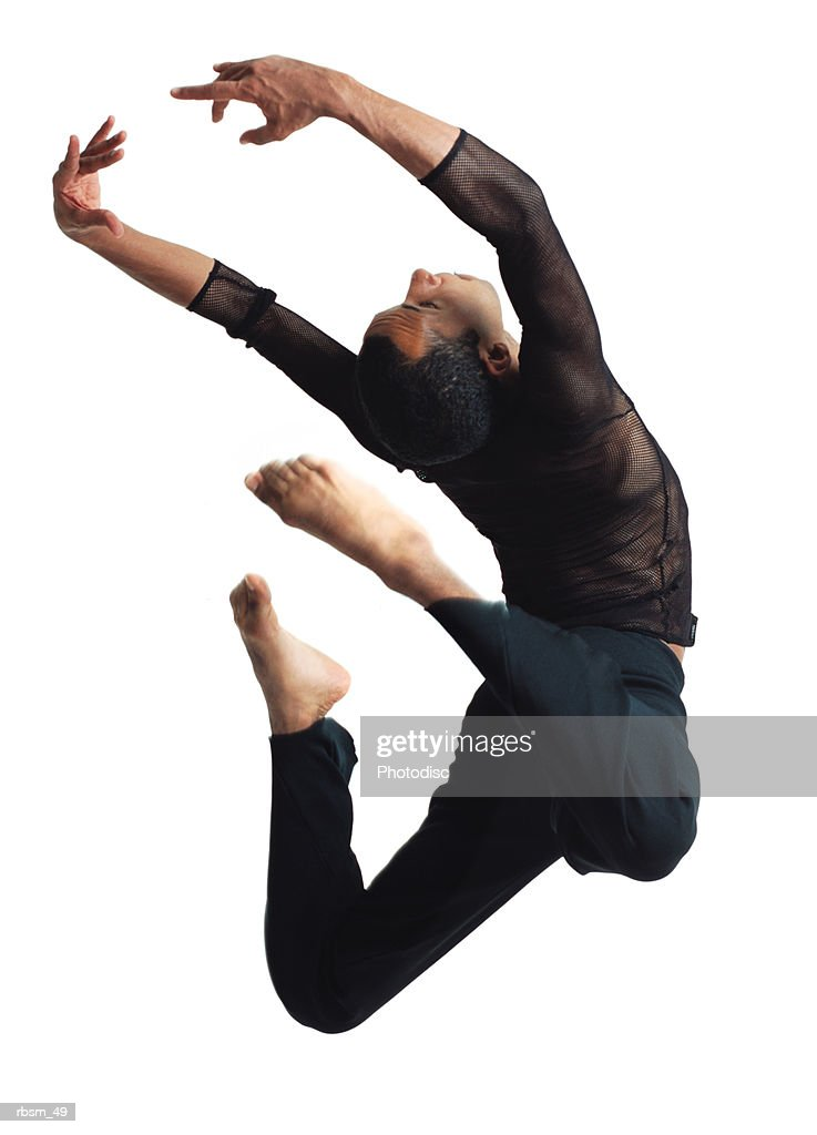 african american man with black mesh shirt and black pants jumping with his back arched and his arms and legs stretched behind him : Foto de stock