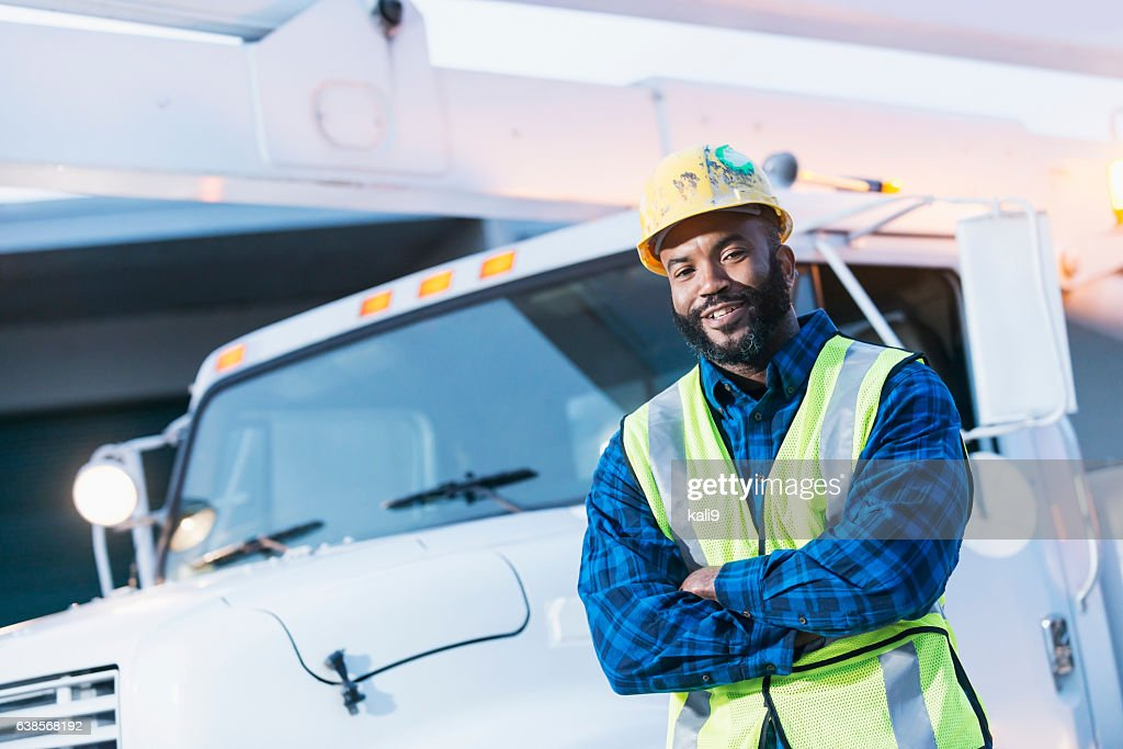 African American man with cherry picker truck : Stock Photo