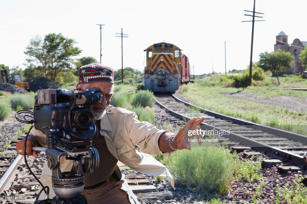African American man with film camera near railroad tracks : Stock Photo