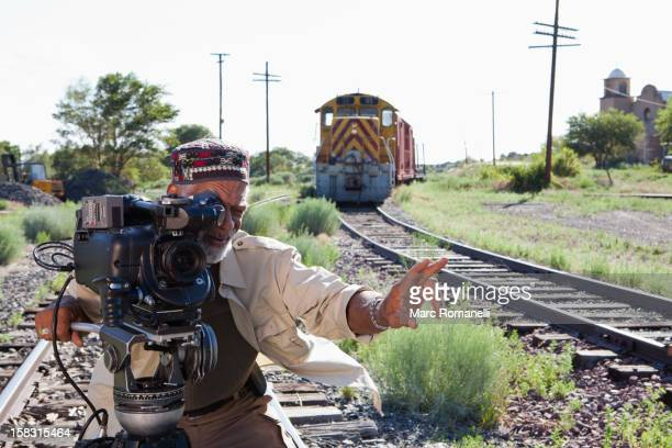 African American man with film camera near railroad tracks