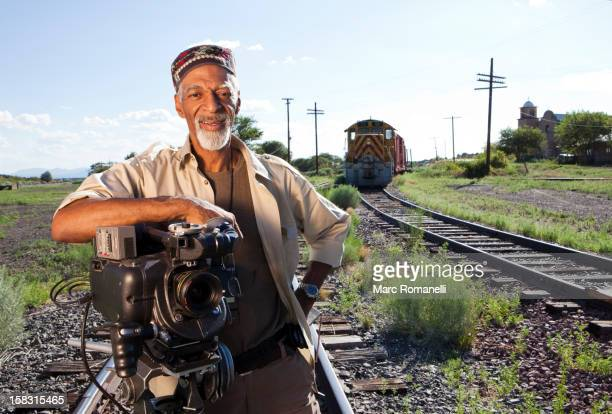 african american man with film camera near railroad tracks - film director stock pictures, royalty-free photos & images