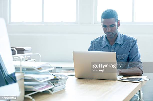 African American man working on a laptop computer.