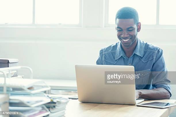 Afroamerikanischer Mann arbeitet auf einem laptop-computer.