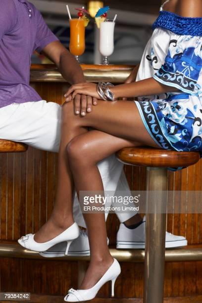 African American man's hand on girlfriend's knee