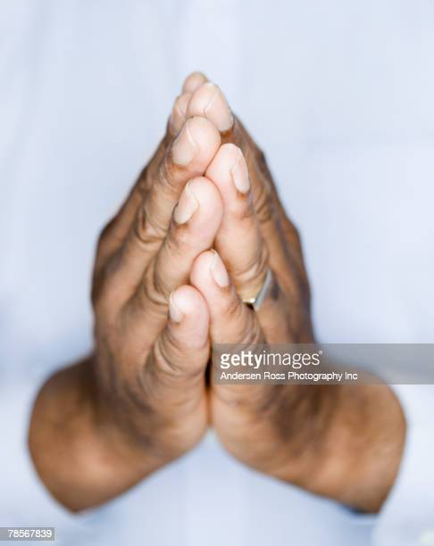 african american man's hands in prayer position - praying hands stock pictures, royalty-free photos & images