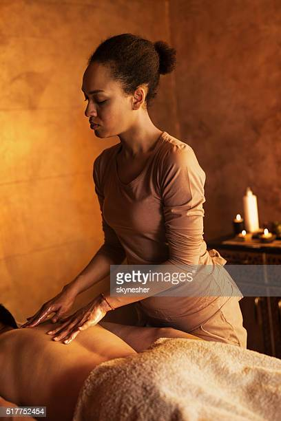 african american massage therapist massaging man's back. - massage black woman stock photos and pictures