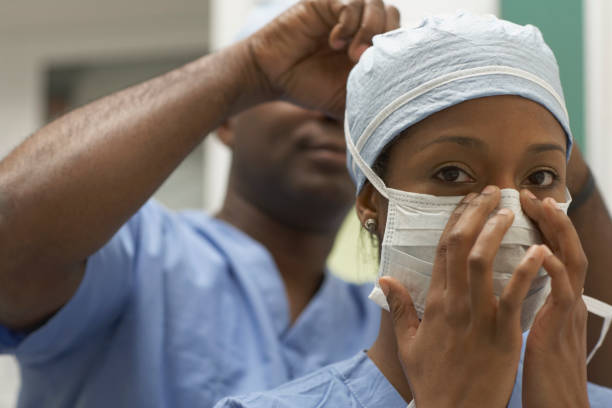 african american medical professional tying coworker's surgical mask - black nurse stock pictures, royalty-free photos & images