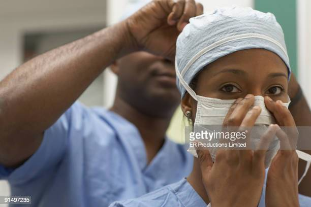 african american medical professional tying coworker's surgical mask - nurse with mask stock pictures, royalty-free photos & images