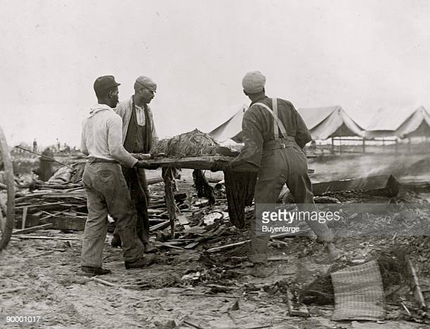 African American men carrying body on stretcher surrounded by wreckage of the hurricane and flood Galveston Texas