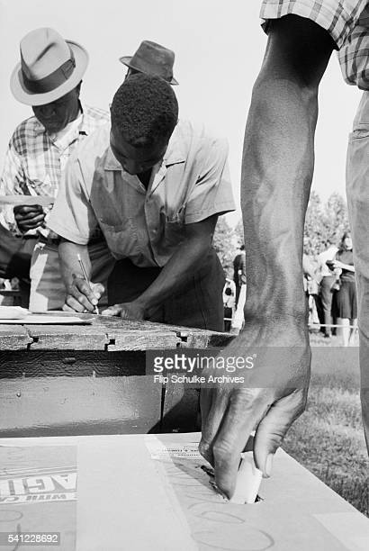 African American men fill out their ballots and drop them in ballot boxes in Alabama after enactment of the Voting Rights Act.
