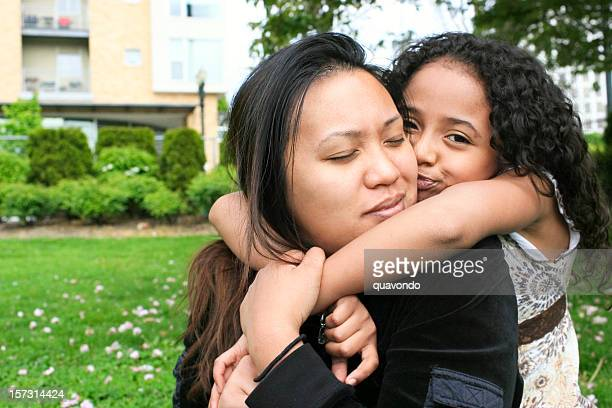 African American Mixed Daughter Kissing Asian Mother on Cheek, Copyspace