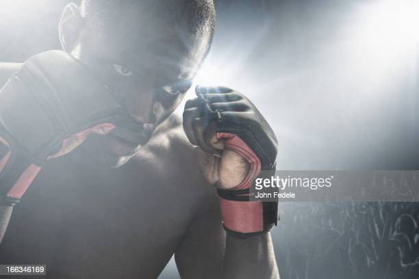 African American MMA boxer with gloves raised