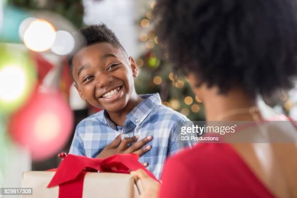 Maman africaine américaine donne son jeune fils un cadeau de Noël