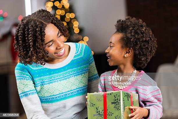 african american mom opening christmas present with preschool age daughter - giving a girl head stock photos and pictures