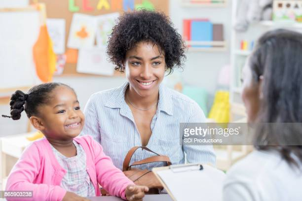 african american mom talks with teacher during conference - genitori foto e immagini stock