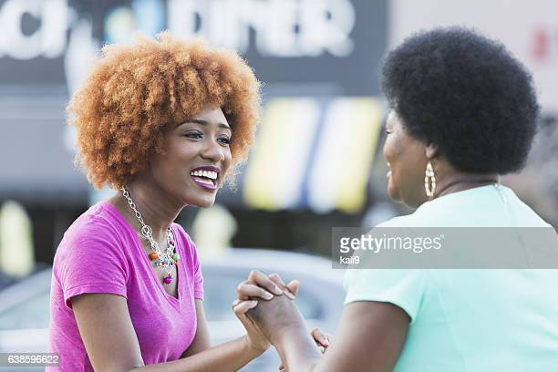African American mother and adult daughter holding hands