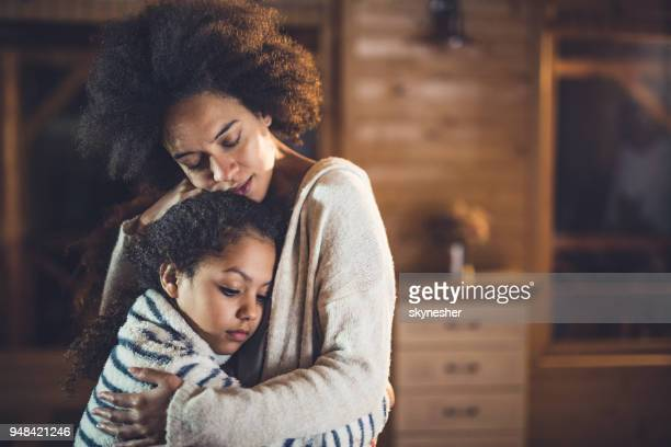 African American mother and daughter embracing at home.