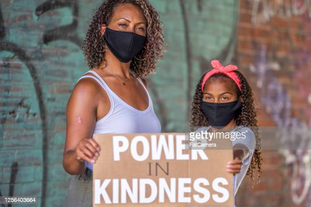 african american mother and daughter holding protest signs - fight for families rally stock pictures, royalty-free photos & images