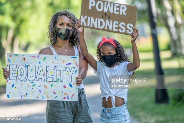 african american mother and daughter holding protest signs - giustizia sociale foto e immagini stock