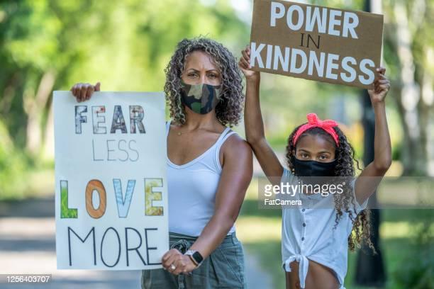 madre e hija afroamericana sosteniendo carteles de protesta - antirracismo fotografías e imágenes de stock