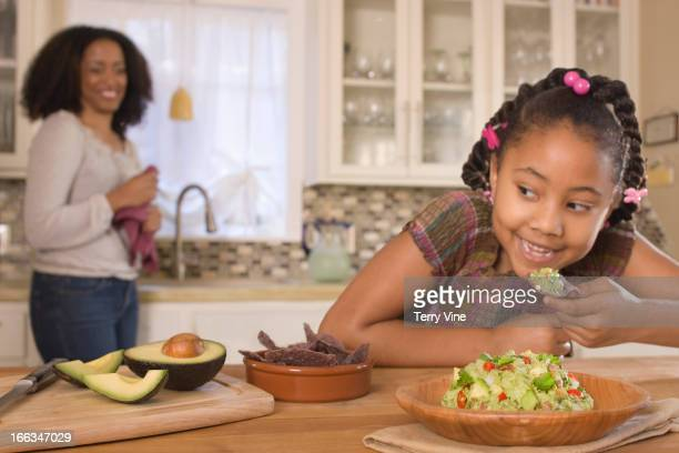 African American mother and daughter making guacamole