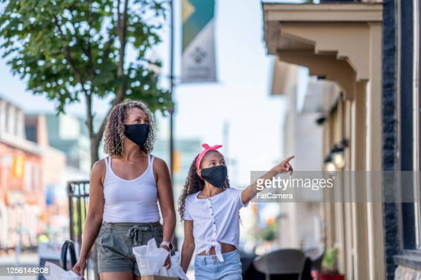 african american mother and daughter shopping downtown while wearing masks - fatcamera stock pictures, royalty-free photos & images