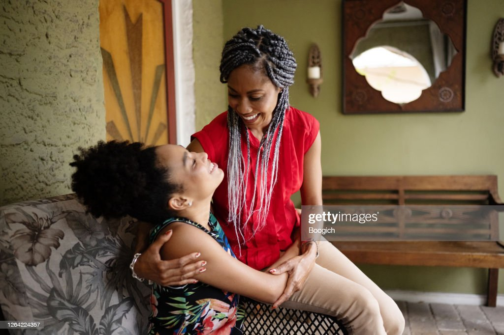 African American Mother and Daughter Sitting Together Outdoors on Front Porch : Stock Photo