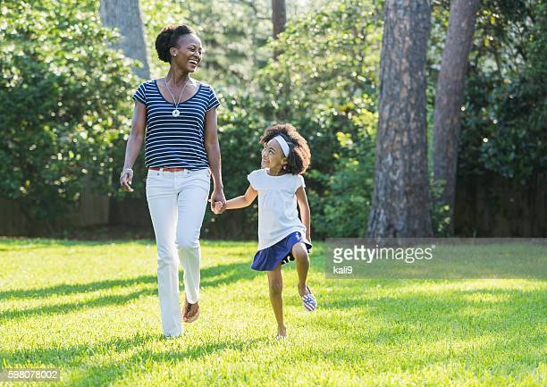 African American mother and daughter skipping, laughing