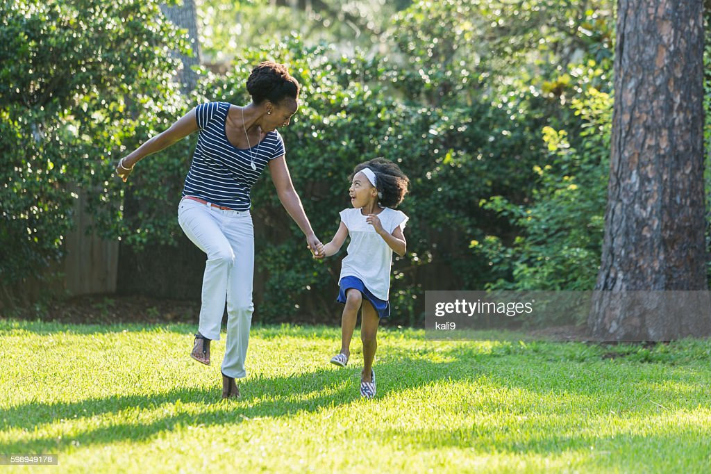 African American mother and daughter skipping, laughing : Stock Photo