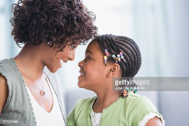 african american mother and daughter smiling at each other - コーンロウ ストックフォトと画像