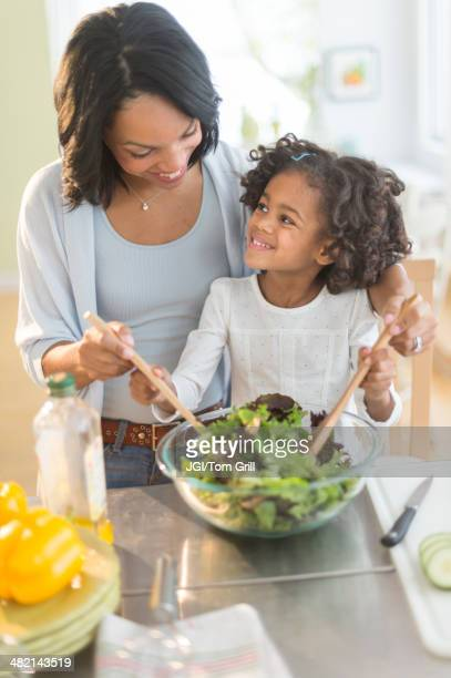African American mother and daughter tossing salad